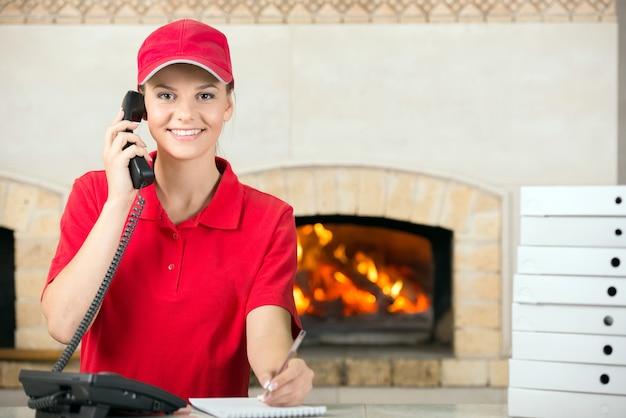 Frau des pizzabehälters und -tagebuchs für das vergeben der bestellung.