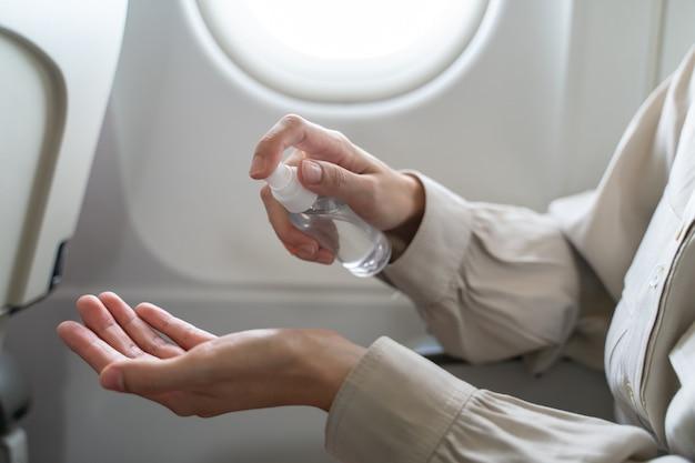 Frau desinfektionsmittel hand auf flugzeug