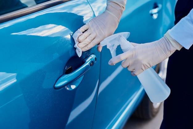 Frau desinfiziert autotürgriff mit einem antibakteriellen spray. auto waschen