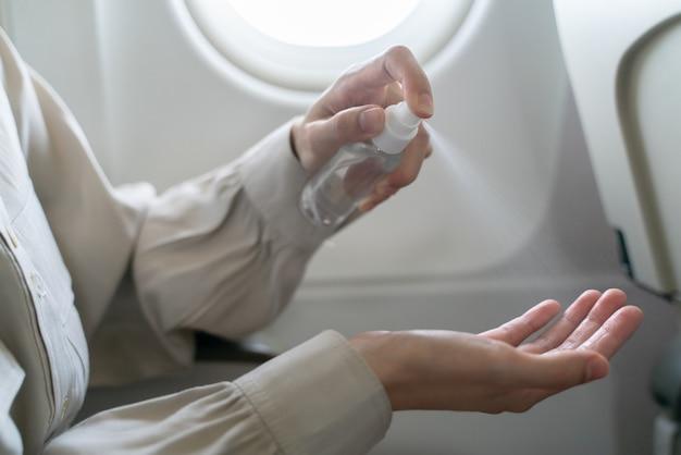 Frau desinfiziert hände tragen alkohol desinfektionsmittel an bord eines flugzeugs