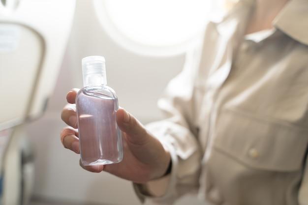Frau desinfiziert hände, tragen gelalkohol an bord eines flugzeugs auf. neue normal-, sicherheits- und reisetransporte während der covid-19-pandemie.