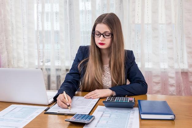 Frau, die 1040 formular ausfüllt, arbeitet im büro