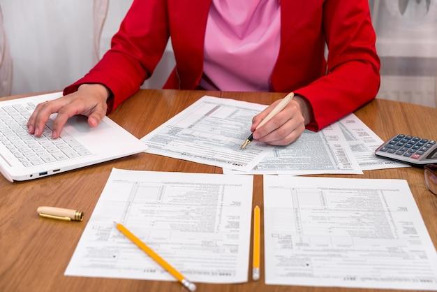 Frau, die 1040 formular ausfüllt und auf laptop tippt