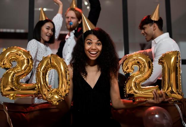 Frau, die 2021 luftballons an der partei hält