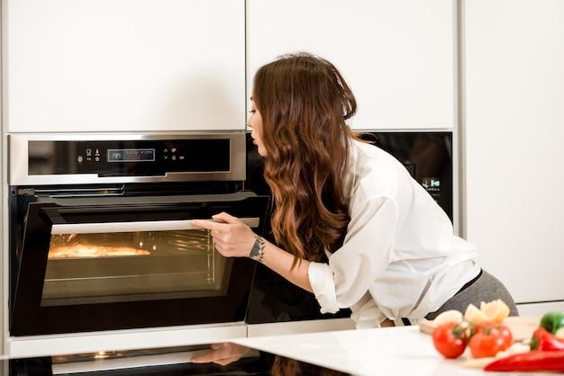 Frau, die abendessen im ofen auf der küche kocht
