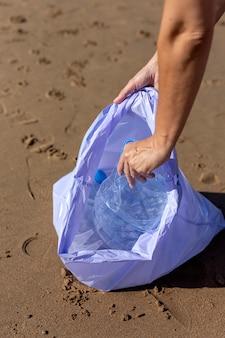 Frau, die abfall und plastik säubern den strand aufhebt