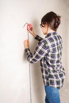 Frau, die abstand auf weißer wand mit maßbandwerkzeug und bleistift misst und markiert