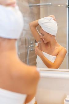 Frau, die achselhöhle nach der dusche rasiert