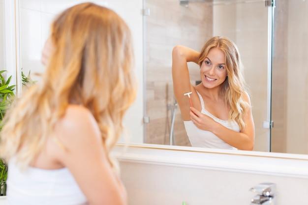 Frau, die achselhöhle vor dem spiegel rasiert
