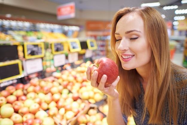 Frau, die äpfel vom lebensmittelgeschäft wählt