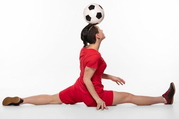Frau, die akrobatik mit fußball tut