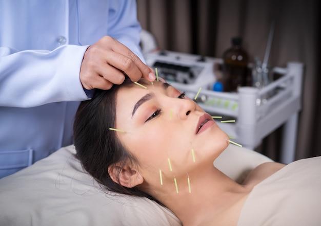 Frau, die akupunkturbehandlung auf gesicht durchmacht