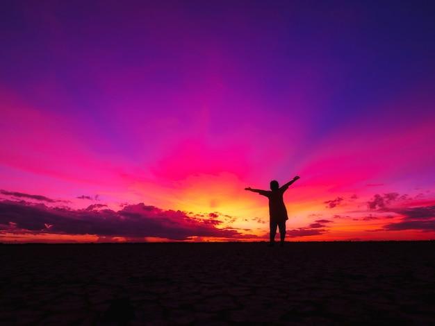 Frau, die allein am feld steht, das der sonne während des schönen sonnenuntergangs gegenübersteht.