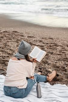 Frau, die allein am strand liest