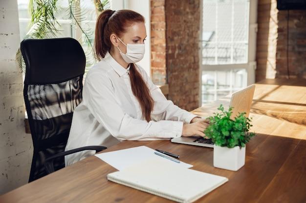 Frau, die allein im büro während des coronavirus oder der koviden quarantäne arbeitet, die gesichtsmaske trägt
