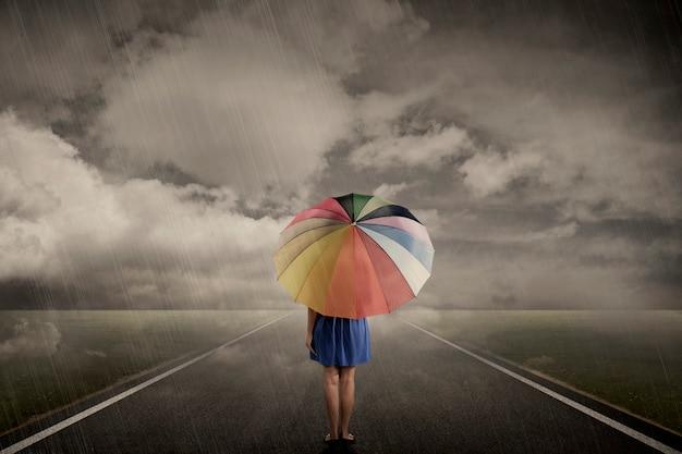Frau, die alleine am regnerischen tag geht
