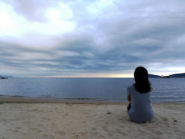 Frau, die alleine auf dem strand unter bewölktem himmel von hinten sitzt