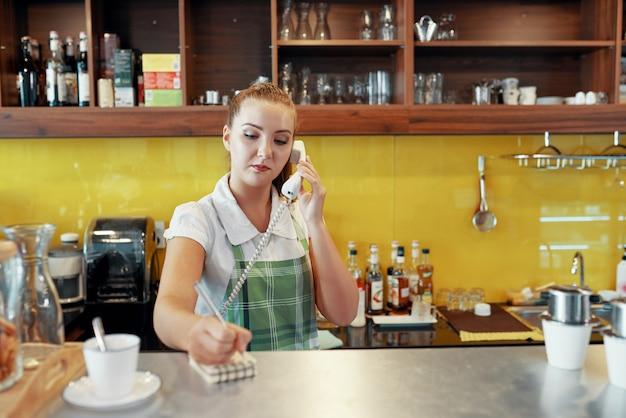 Frau, die als barista nimmt telefonauftrag arbeitet