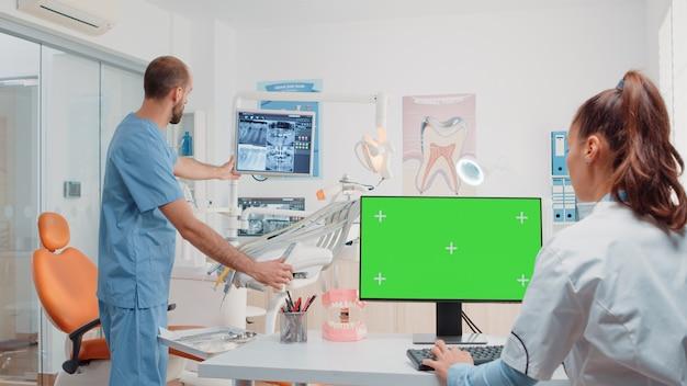 Frau, die als zahnarzt mit grünem bildschirm auf monitor arbeitet
