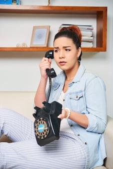 Frau, die am alten telefon spricht