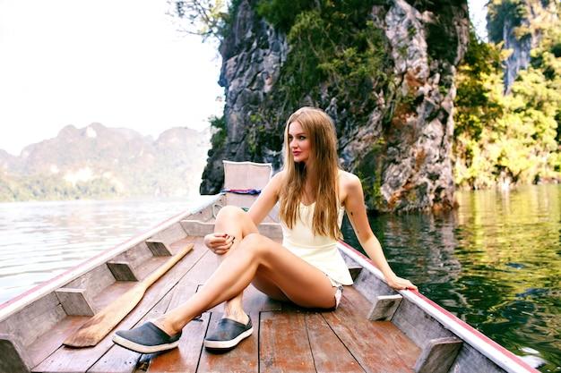 Frau, die am alten traditionellen thailändischen bootsende sitzt, der nationalpark khao sok erkundet