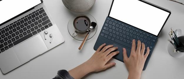 Frau, die am arbeitsbereich mit digitalem tablet, laptop und briefpapier des modells arbeitet