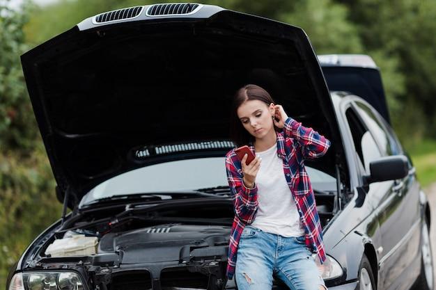 Frau, die am auto sitzt und telefon überprüft