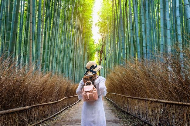 Frau, die am bambuswald in kyoto, japan geht.