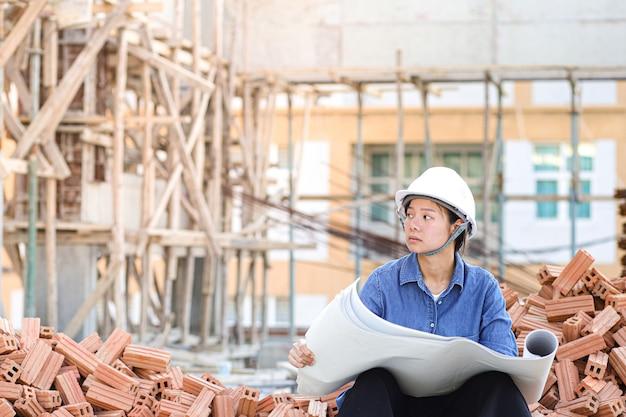 Frau, die am baubereich arbeitet, der blaupause auf händen hält. weiblicher ingenieur, der auf ziegelhaufen sitzt.