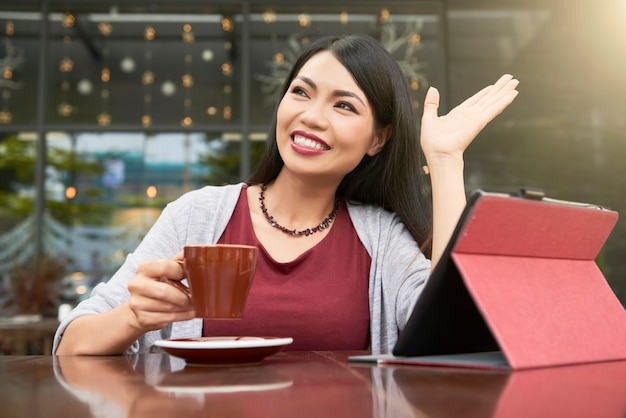 Frau, die am café guten tag sagt