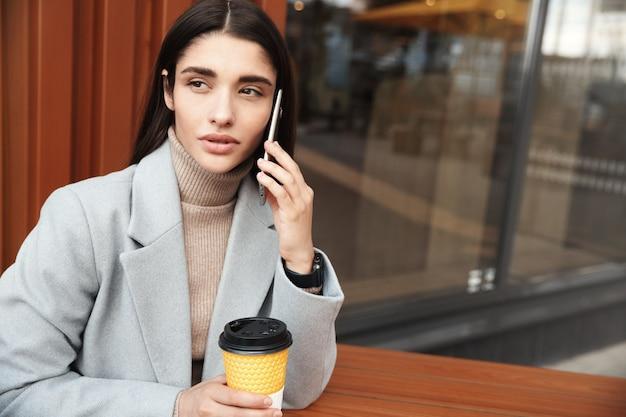 Frau, die am café sitzt und auf handy spricht. geschäftsfrau, die mit kunden während der arbeit von einem café spricht.