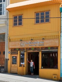 Frau, die am eingang eines restaurants, valparaiso, chile steht