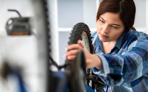 Frau, die am fahrradrad arbeitet
