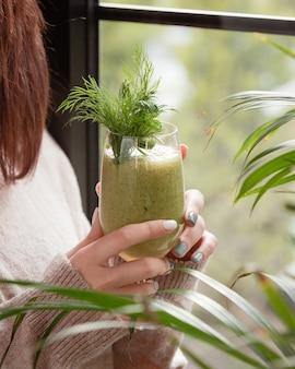 Frau, die am fenster einen grünen detox smoothie mit dills hält.