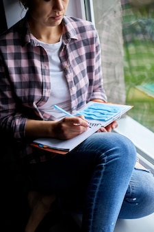 Frau, die am fenster sitzt und in notizbuchplan schreibt, um liste nach quarantäneende, coronovirus-ende zu tun