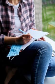 Frau, die am fenster sitzt und in notizbuchplan schreibt
