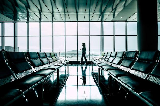 Frau, die am flughafen-gate spazieren geht und den flugstart für geschäfts- oder urlaubsaktivitäten wartet - flugverspätung oder storniert - rechte und versicherung für reisende