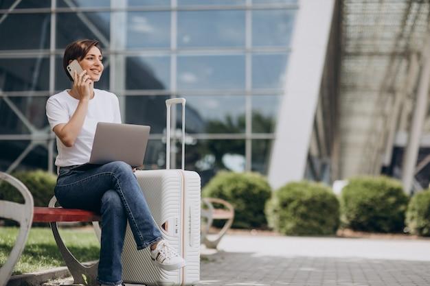 Frau, die am flughafen reist und am computer arbeitet