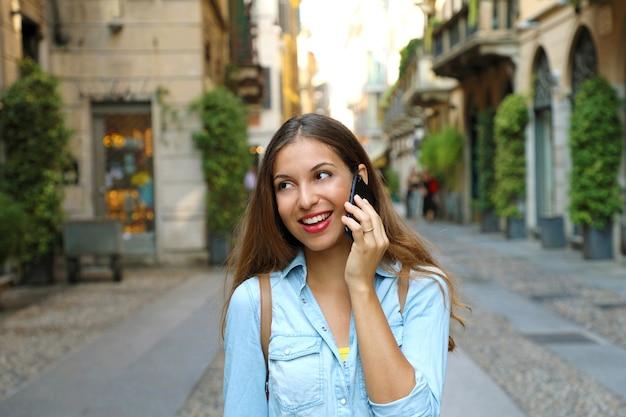 Frau, die am handy an der stadtstraße in mailand in italien spricht