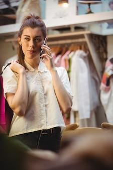 Frau, die am handy beim einkauf spricht