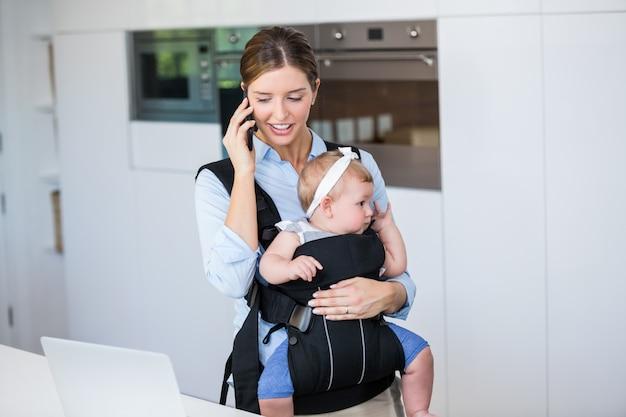 Frau, die am handy beim tragen des babys spricht