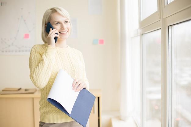 Frau, die am handy im büro spricht