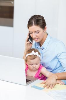 Frau, die am handy sitzt mit baby spricht