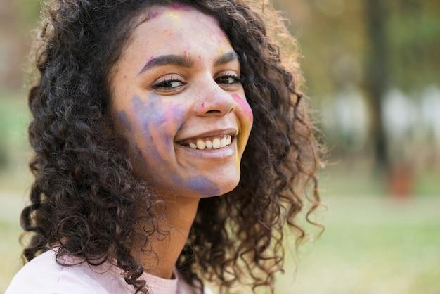 Frau, die am holi festival mit schönem lächeln aufwirft