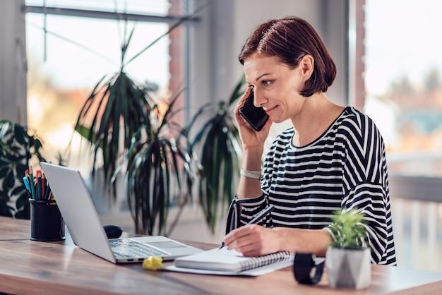Frau, die am intelligenten telefon im büro spricht
