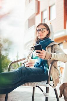 Frau, die am intelligenten telefon schreibt