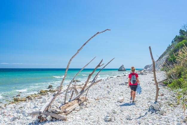 Frau, die am italienischen strand geht. ungleiche küste von conero, kiesstrand, türkisfarbenes wasser, echte menschen, rückansicht, sonniger tag, urlaub in italien