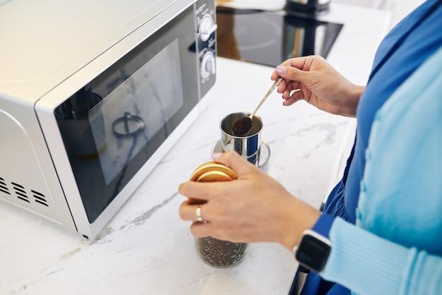 Frau, die am küchentisch im büro steht und löffel des gemahlenen kaffees in tasse setzt