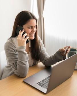 Frau, die am laptop arbeitet und am telefon spricht