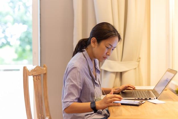 Frau, die am laptop im hotelzimmer arbeitet.